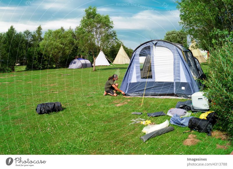 Camping - Camping. Man pitching a tent in a meadow in the summer active activity Adults Adventure Outdoors Lifestyle Summer Camping site Landscape Day gear