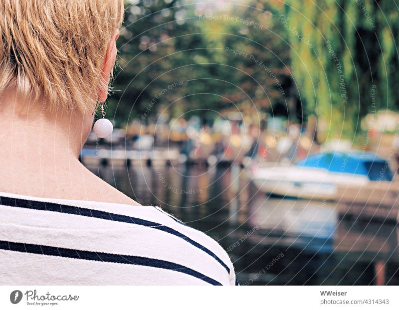 A woman with a short haircut and a fashionable earring looks over to a boat harbour with a lot of people Woman Lady Back Summer Modern Chic Stripe Maritime