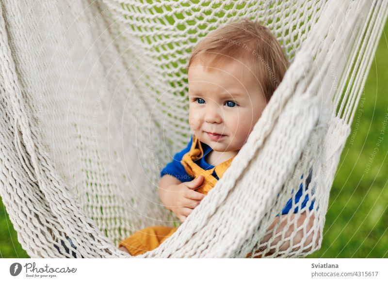A little boy sits in a hammock on a summer day in the garden baby toddler child sun green nature summertime sunbathing relax outside park happy sitting cute