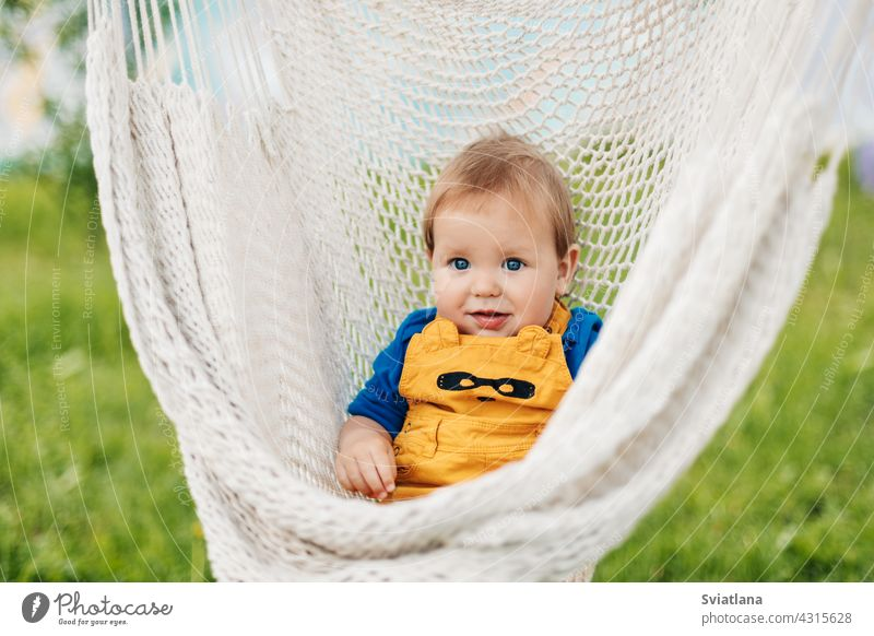 A little boy sits in a hammock and looks at the camera on a summer day in the garden baby toddler child sun green nature summertime sunbathing relax outside