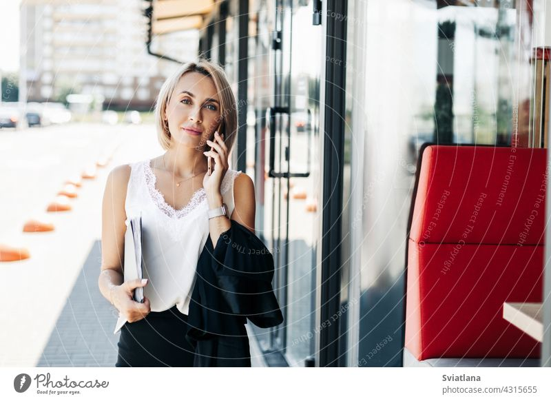A beautiful businesswoman, talking on the phone in the city, holding a folder with documents street portrait standing girl lifestyle executive young success job