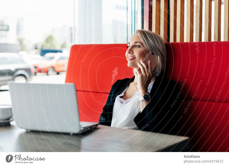An attractive girl is talking on a mobile phone and smiling, sitting alone in a cafe female tablet businesswoman work coffee happy computer working