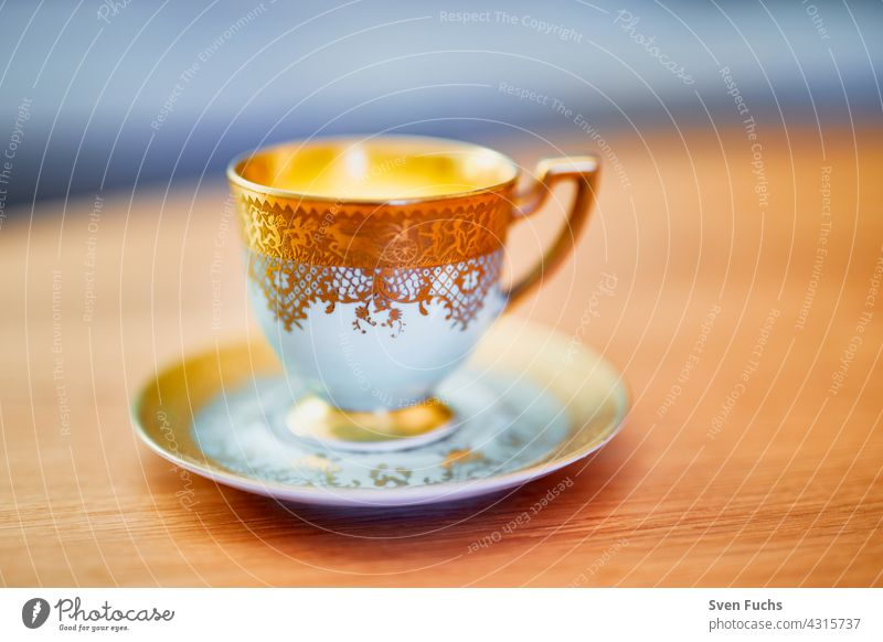 Coffee cup and saucer with gold decoration stand on a wooden table Cup gold edge Crockery Mocha Porcelain Old fashioned Noble Gold Festive Saucer saucers Plate