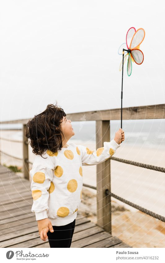 Child holding windmill toy on the beach Caucasian Girl 1 - 3 years Wind Windmill Playing Leisure and hobbies Joy Lifestyle Infancy Toddler Colour photo