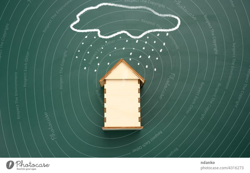 a wooden house and a drawn cloud with rain with white chalk on a green chalk board. insurance home real estate business property safety mortgage protection
