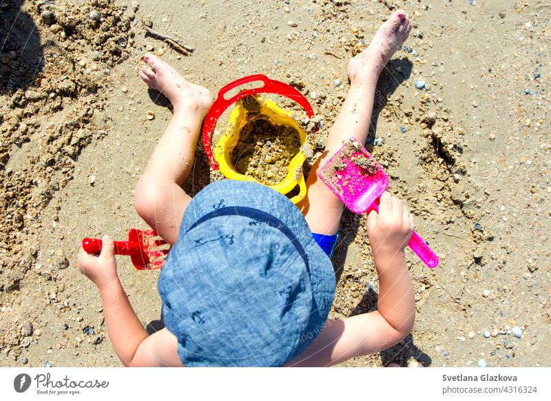 child playing with sand, shovel, bucket beach baby castle summer little building toddler kid vacation joy leisure toys childhood sandcastle cute fun nature boy