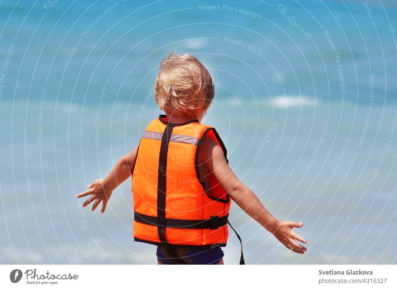 Safety of life concept. Little caucasian boy uses a life jacket on a summer beach against the backdrop of the sea waves. caucasian boy beach safety of life