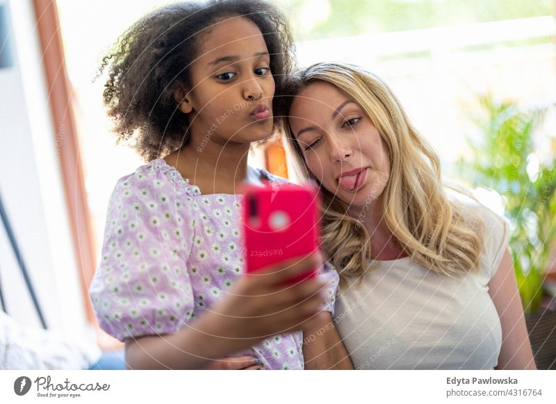 Mother and her young daughter taking a selfie at home mother child family multi-ethnic mixed race family diverse family diversity afro real people millennial