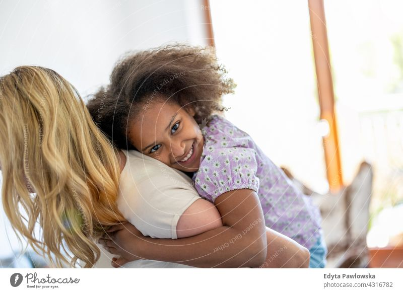 Mother and daughter having fun together at home mother child family multi-ethnic mixed race family diverse family diversity afro real people millennial hair
