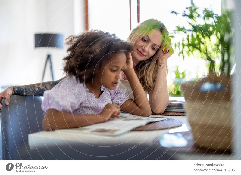 Mother helping daughter with homework mother child family multi-ethnic mixed race family diverse family diversity afro real people millennial hair girl children