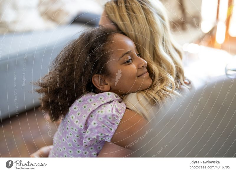 Mother and daughter hugging at home mother child family multi-ethnic mixed race family diverse family diversity afro real people millennial hair girl children