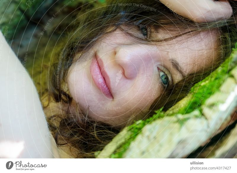 Portrait of a beautiful dark-haired young sexy woman lying happily contentedly in bed of moss in the forest with in an old willow tree with naked shoulders and deep peace in the smile