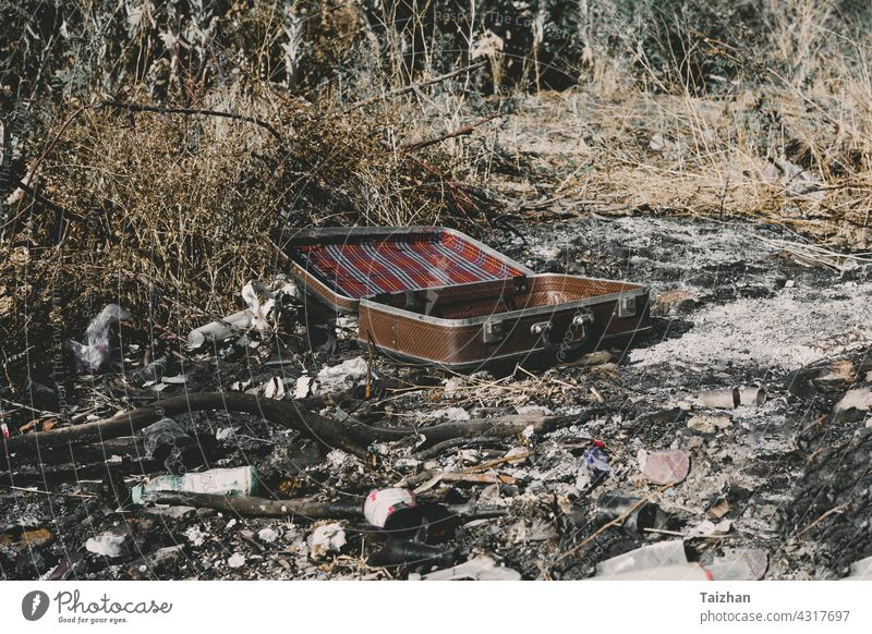 An old weathered vintage suitcase left on the ashes garbage outdoors concepts currency destruction finance freedom ideas lifestyles no people occupation