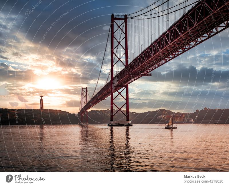 Ponte 25 de Abril Bridge in Lisbon during Sunset with ship and jesus monument, cloudy sky portugal ponte 25 de abril sunset lisbon bridge river city