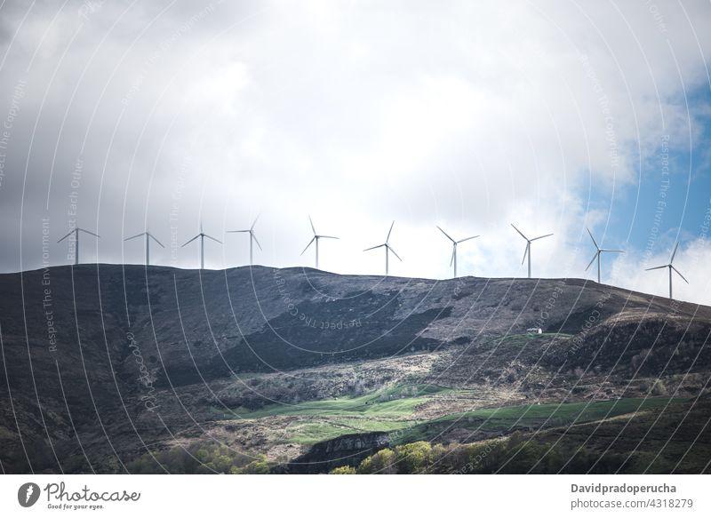 Windmill turbines on grassy hilly terrain windmill power hillside valley energy alternative nature plant propeller landscape environment cantabria spain