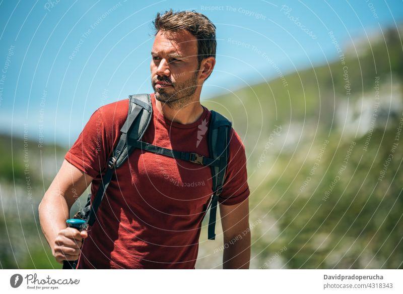 Male hiker walking with trekking poles in mountainous terrain tourist highland backpack rock tourism nature traveler adventure explore stick activity wanderlust