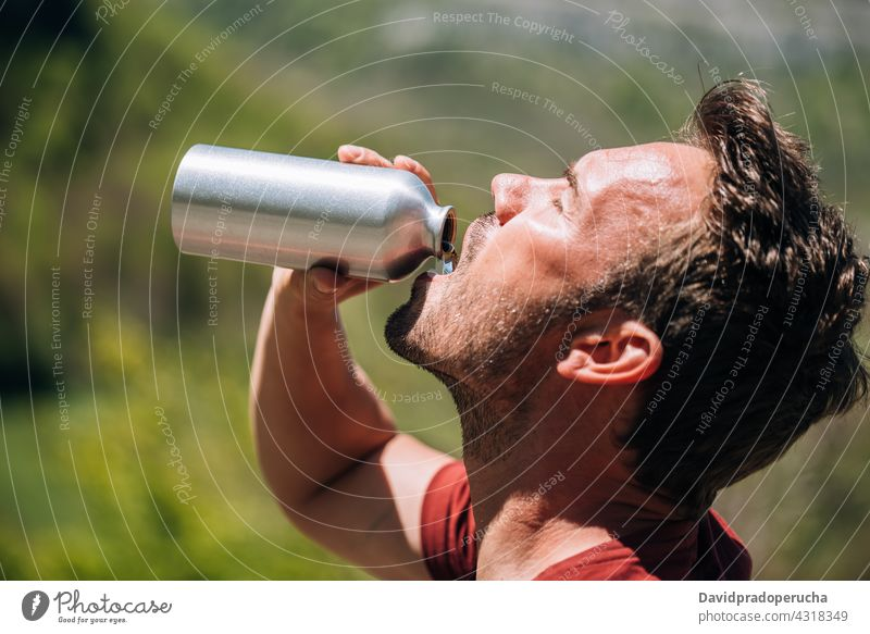 Thirsty man drinking water from reusable bottle tourist thirst reuse zero waste tourism break adventure hot eco friendly sustainable environment traveler