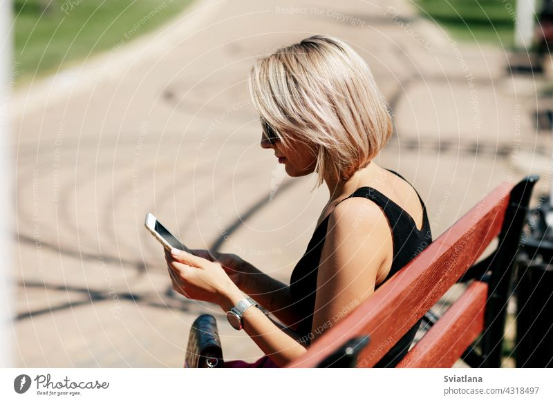 A young woman takes a selfie sitting on a park bench, adjusts her makeup and hairstyle, looking at her reflection on the screen taking phone portrait happy girl
