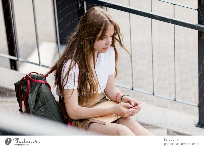 Cute girl sitting on the stairs outside the campus after college class and chatting with her friends teenager phone using backpack school book messaging young