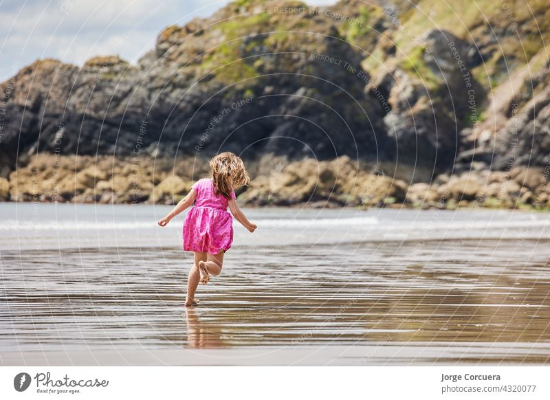 Hispanic girl running along the beach with big rocks in the background sand playing adorable toddler kid summer young child childhood sea person cute caucasian