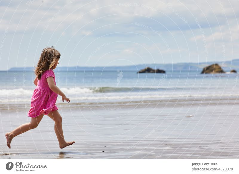 girl running on the beach with a clear horizon and great copy space sand playing adorable toddler kid summer young child childhood sea person cute caucasian