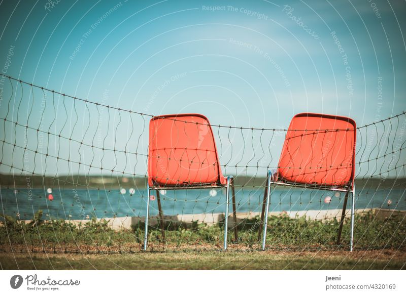 Two unoccupied chairs for lifeguards at the lakeshore Lake Lakeside Water watch vacation Lifeguard Rescue Observe observation Meadow Fence cordon Blue sky
