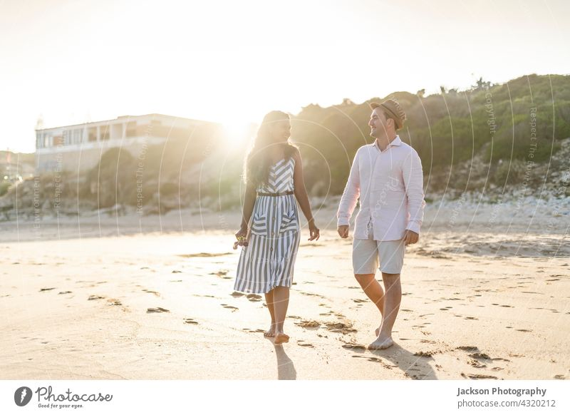 Young couple enjoying time together on the beach people fun love nature lovers summer algarve portugal kiss walk smile active affectionate handsome boyfriend