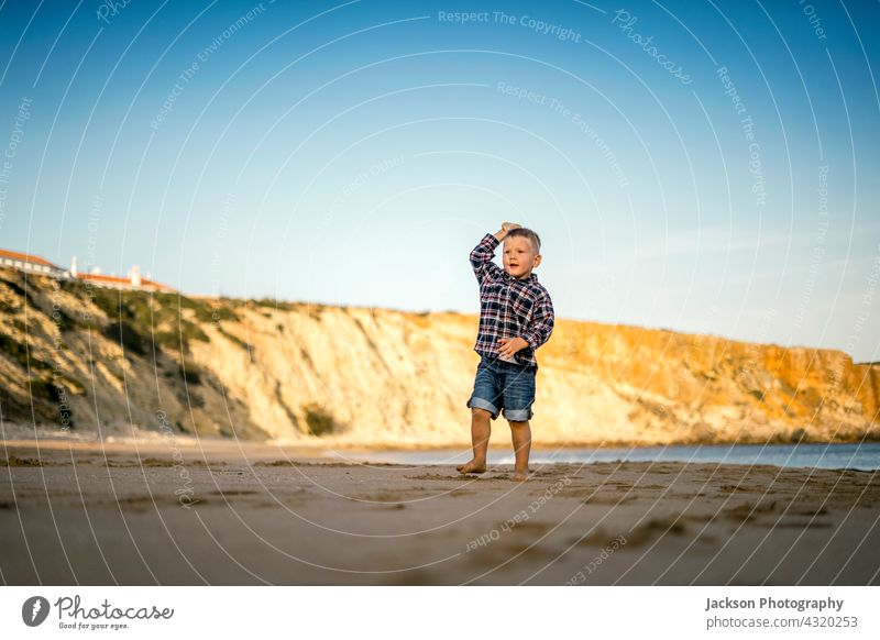 Small boy throwing stones on the beach by the sunset play toddler copy space sagres portugal barefoot son horizontal baby sunny run seaside summertime playful