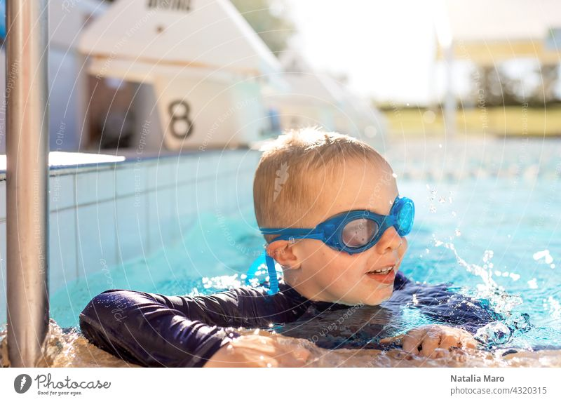 Child in goggles in swimming pool blue boy vacation water outdoor child summer happy kid joy smile wet recreation play leisure sunny fun swimmer cheerful cute