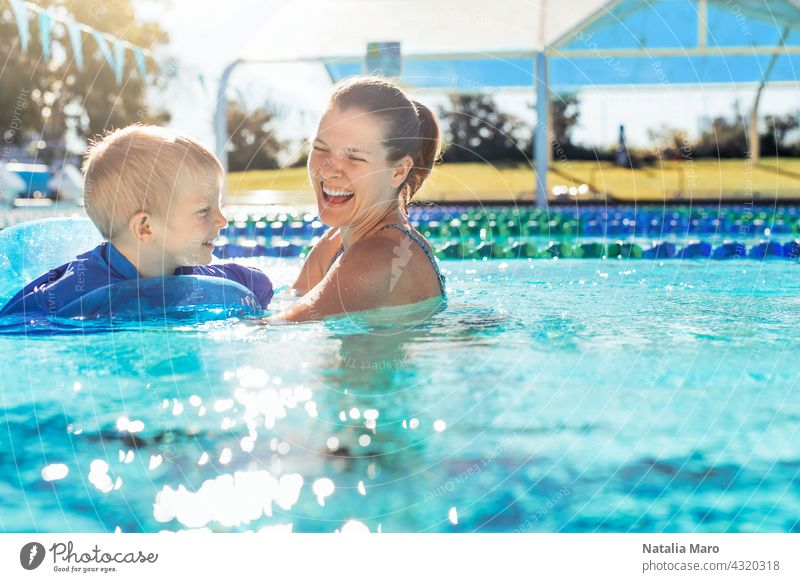 Mother and child in swimming pool woman boy mother vacation tube water outdoor summer happy blue kid joy female smile wet recreation play leisure sunny fun