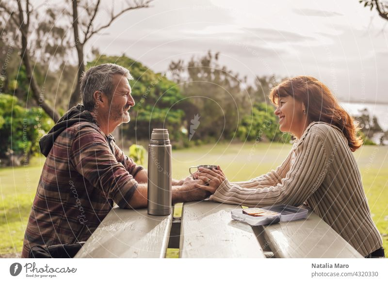 Middle-aged couple sitting on the benches with table in park and drinking tea. middle-aged woman happy ocean together leisure love adult pretty relationship
