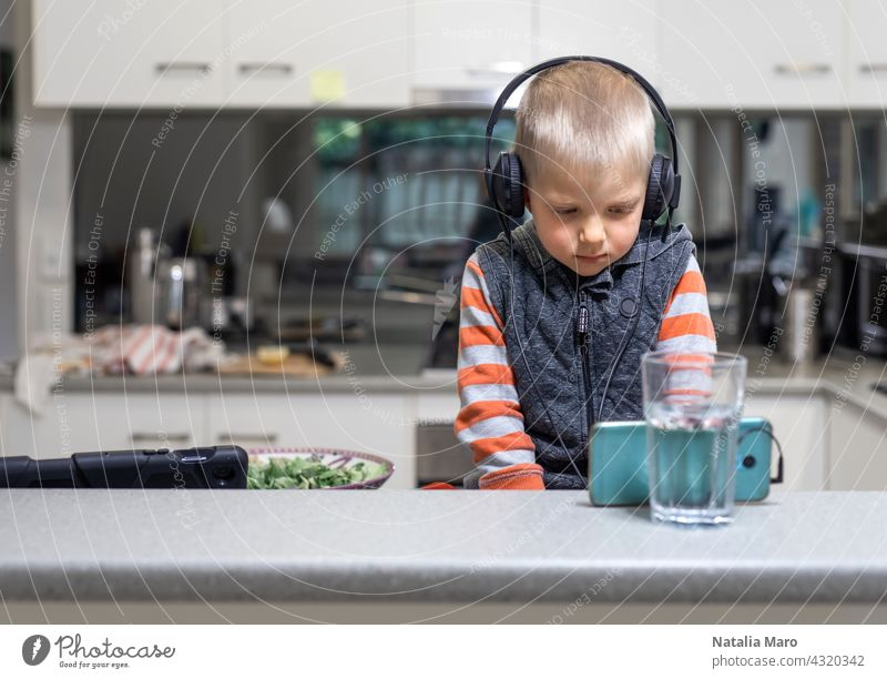 Little child boy wares headphone and playing the cell phone on the kitchen table computer son tablet mobile phone studying cook house internet technology