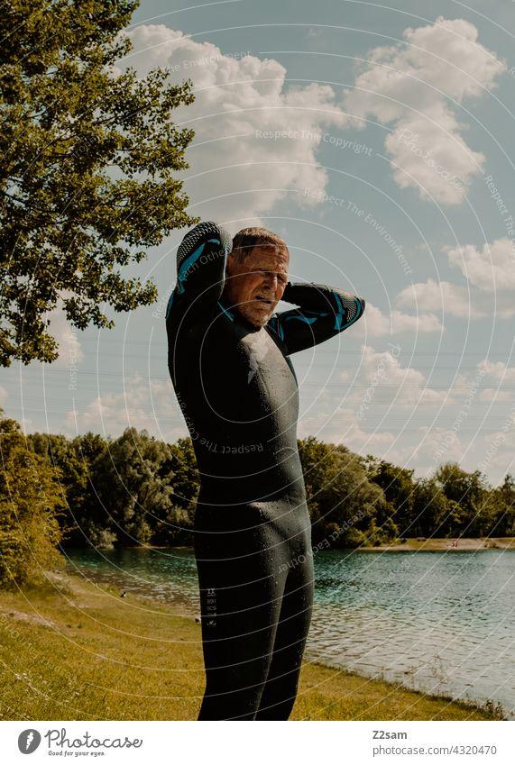 Triathlet am See triathlon schwimmen sport wassersport triathlet wiese rasen badesee openwater swimming natur wärme sommer blauerhimmel wolken neoprenanzug