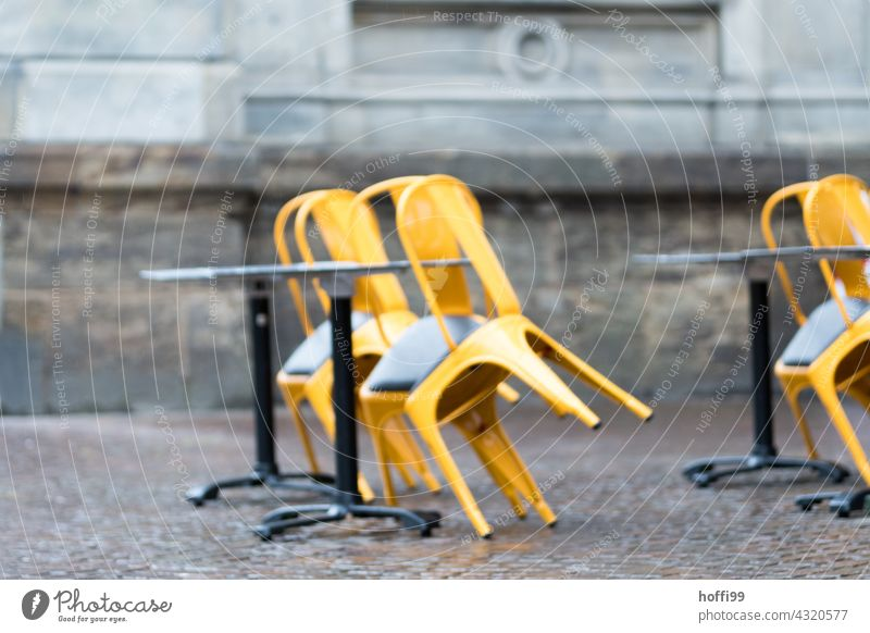 chairs leaning against tables in a street café - end of season End of the season Bistro Closed Bad weather Autumn Rain Café Sidewalk café Terrace Table Chair