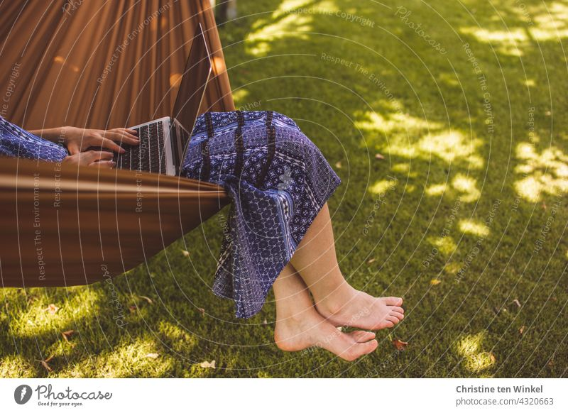 A young woman in a blue summer dress sits comfortably in a hammock in the garden, works on the notebook and lets her feet dangle Woman Young woman Hammock Cozy