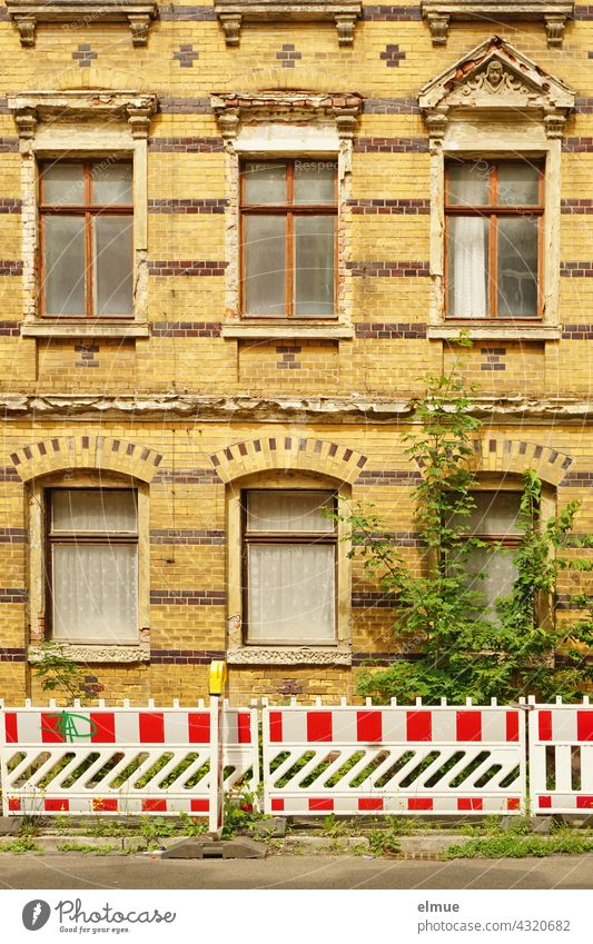 red-white barrier beacons in front of a richly decorated but slowly decaying residential house with yellow-brown clinker facade from the Gründerzeit / dilapidated / lost place