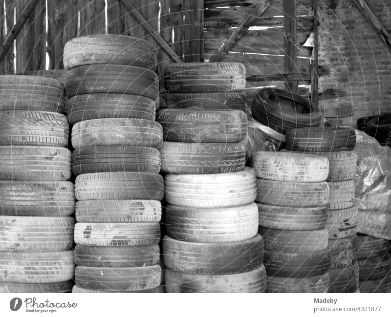 Stacked old car tires in front of a workshop in Adapazari in the province of Sakarya in Turkey, photographed in neo-realistic black-and-white. Tire Car tire