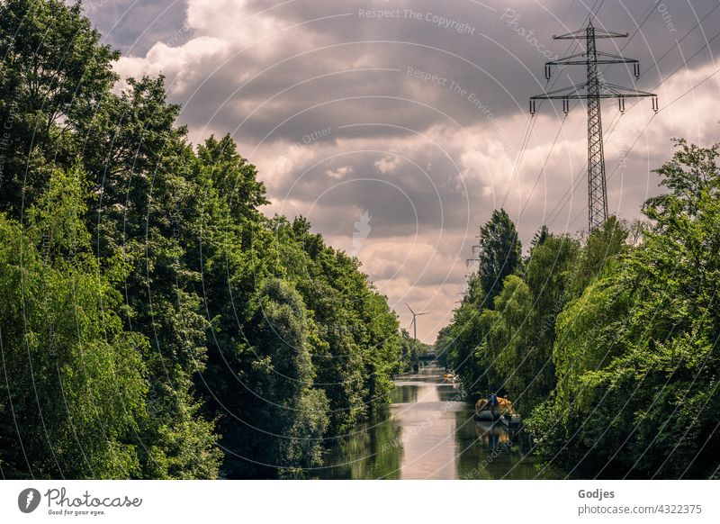 River between green trees with view of wind turbine and power pole, energy turnaround Nature Electricity Wind energy plant High voltage power line