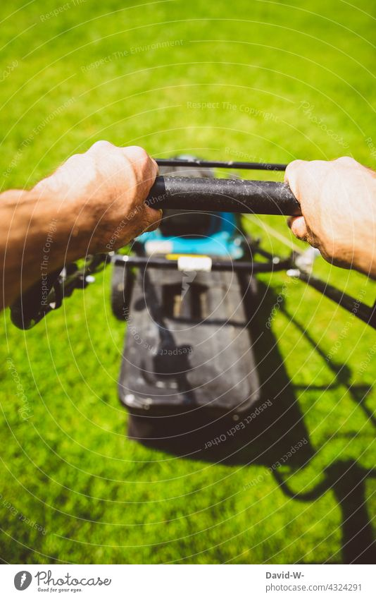 Man mowing the lawn with a lawn mower in the sunshine Lawnmower mares hands Gardening Summer Mow the lawn