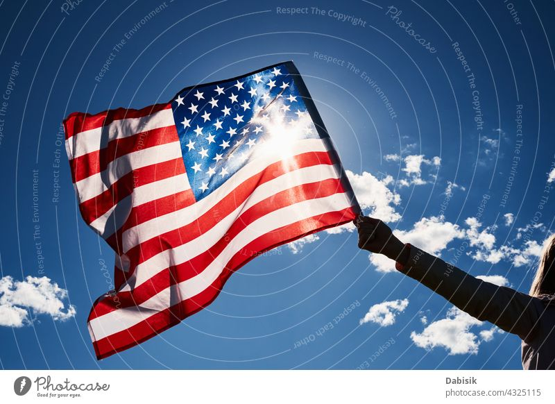 Waving usa flag in hand against blue sky american outdoor 4th july person waving travel people summer day stars stripes background beautiful independence