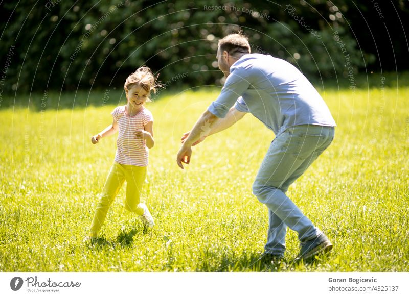 Father chasing his little daughter while playing in the park cheerful father running people outdoors family offspring dad happy parenting smiling girl child