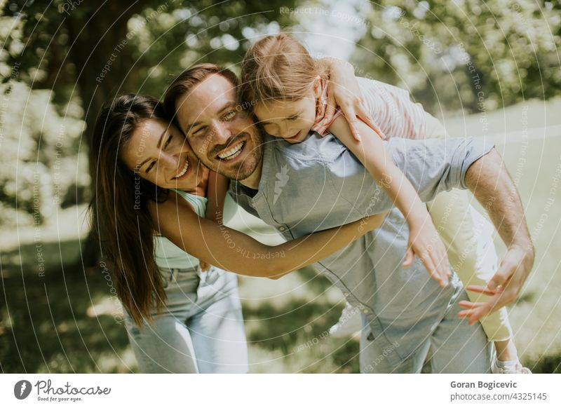 Happy young family with cute little daughter having fun in the park on a sunny day adult beautiful caucasian cheerful child childhood couple dad enjoyment