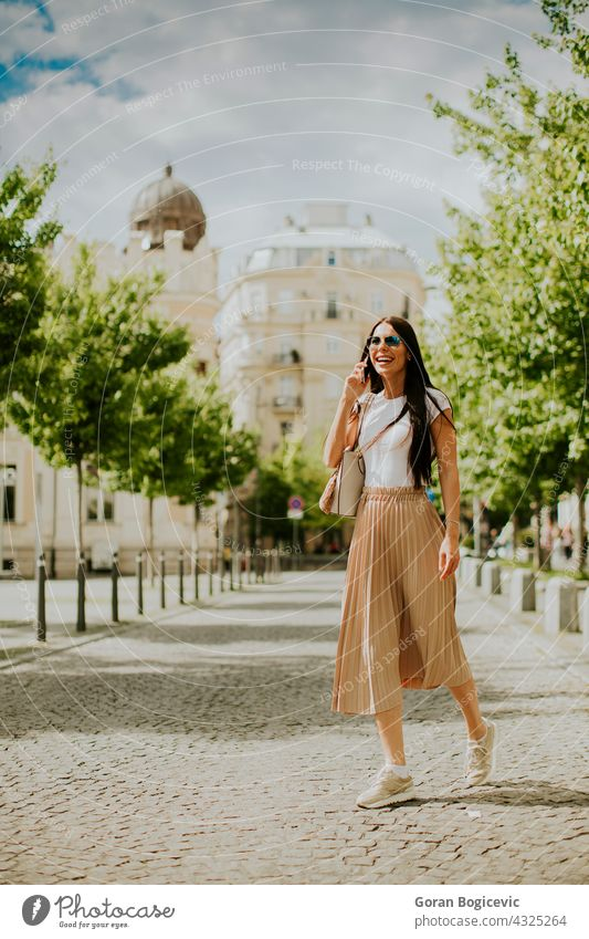 Young woman using a mobile phone while walking on the street 20s adult attractive bag beautiful sunglasses busy call casual caucasian cell city communication
