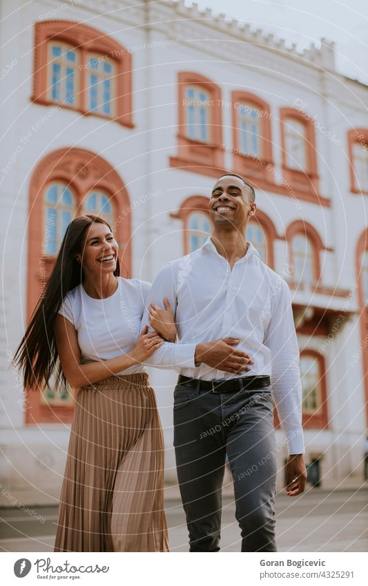 Young multiethnic couple walking on the street love woman young happy relationship together people urban romance city caucasian beautiful embracing female