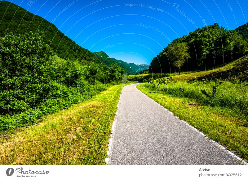 2021 06 13 Lessini road in the valley spring country nature landscape green asphalt summer rural way countryside sky highway travel blue grass field tree