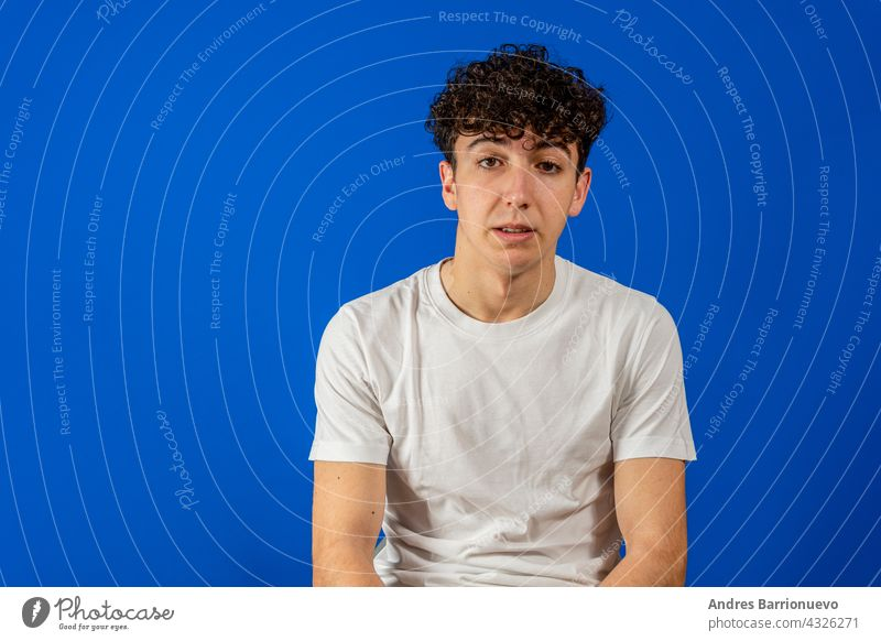 Portrait Of A Serious Young Man Standing On Blue Background man portrait curly face guy background blue person young male isolated handsome studio fashion