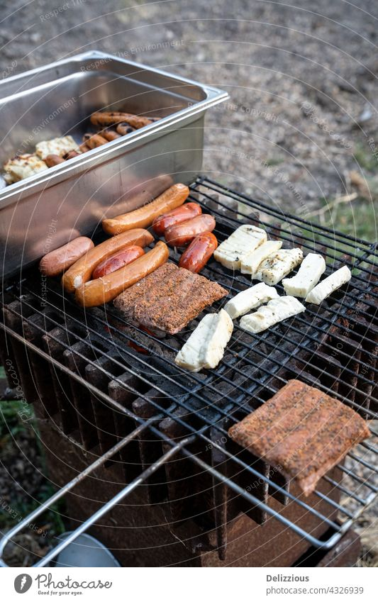 Barbequing sausages on hot coals outside, two grills with meat, cheese and sausages haloumi haloumni grilled cheese barbeque barbecue bbq tongs turn turning