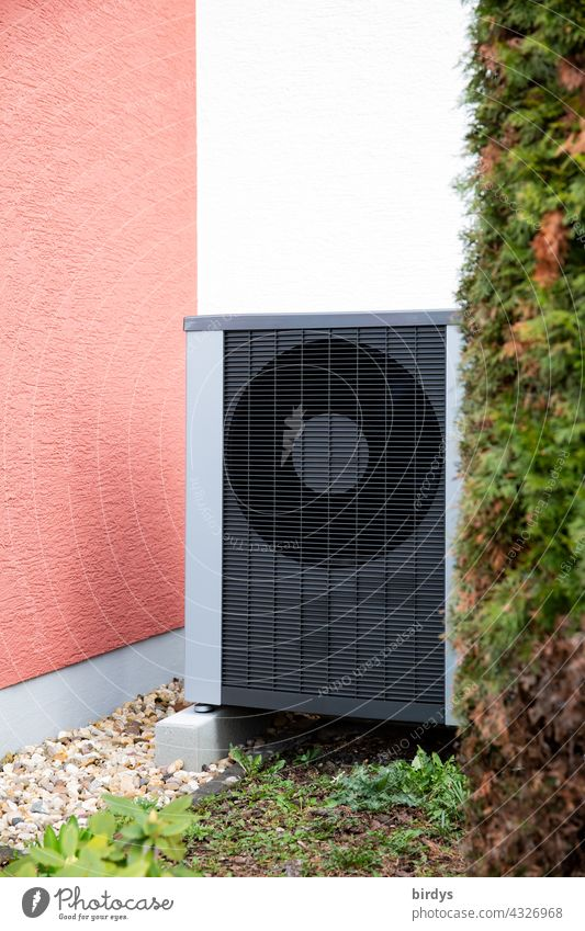 Heat pump in the front yard of a house. Air-to-water heat pump Innovative Air source heat pump plants Green Red bush house corner Fans