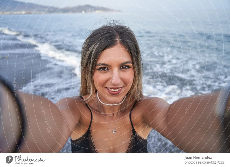 young woman takes a selfie with the mobile and the sea in the background pretty smart phone smartphone photo picture lady smile nice beauty posing mobile phone