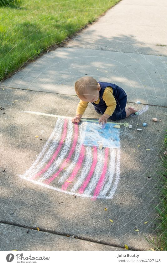 One year old baby next to chalk drawing of the American flag; toddler is crawling and playing with chalk on the 4th of July 4th of july american flag usa